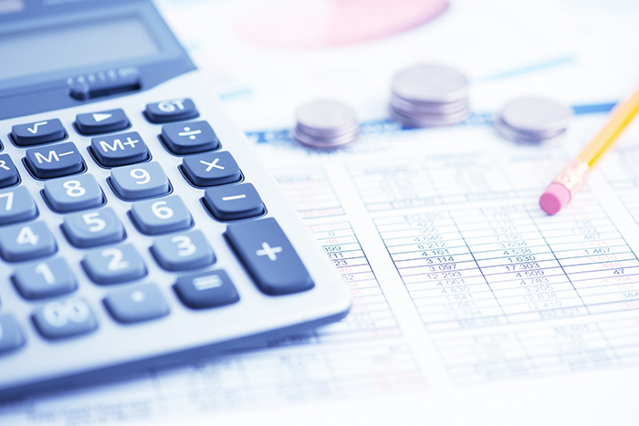 contenção - calculadora e algumas moedas sobre uma planilha impressa