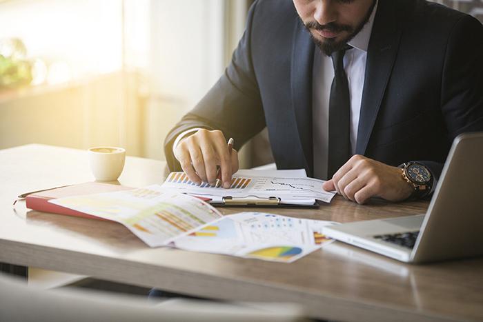 indicadores mercadológicos - homem de terno e gravata em uma mesa de escritório analisando gráficos e tabelas