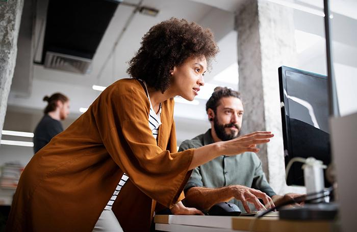 erp industrial - mulher de pé ao lado de homem sentado em frente a um computador, para o qual ambos estão olhando