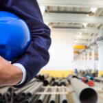 mão de obra qualificada - homem de terno segurando capacete em uma fábrica