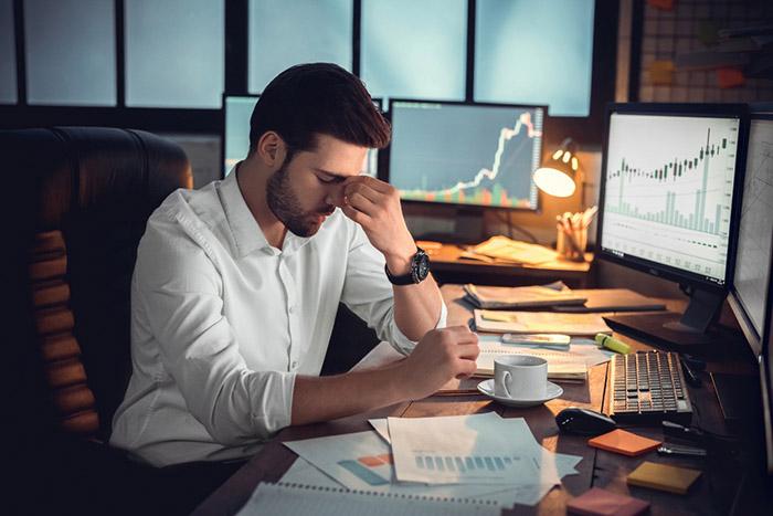 perda financeira - homem com a mão no rosto em uma mesa de escritório com monitores apresentando gráficos e dados