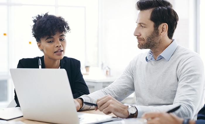 previsão de demanda - mulher e homem sentados lado a lado conversando em frente a um notebook
