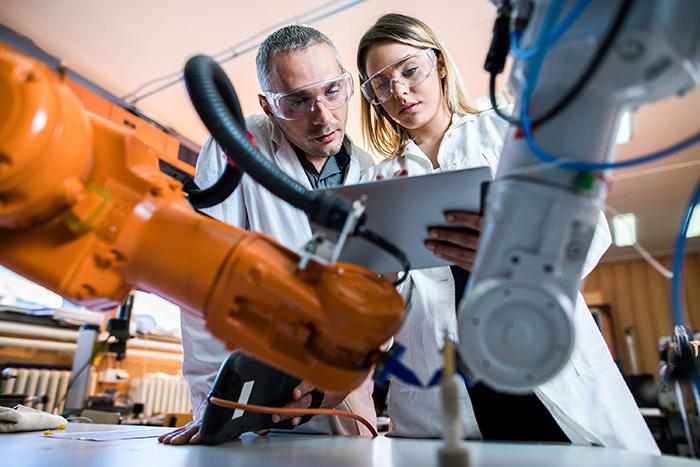 por que a tecnologia é importante - homem e mulher trabalhando em uma indústria utilizando tecnologia