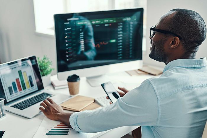 análise de mercado -  homem em uma mesa de escritório acompanhando gráficos e dados em um computador e um notebook paralelamente
