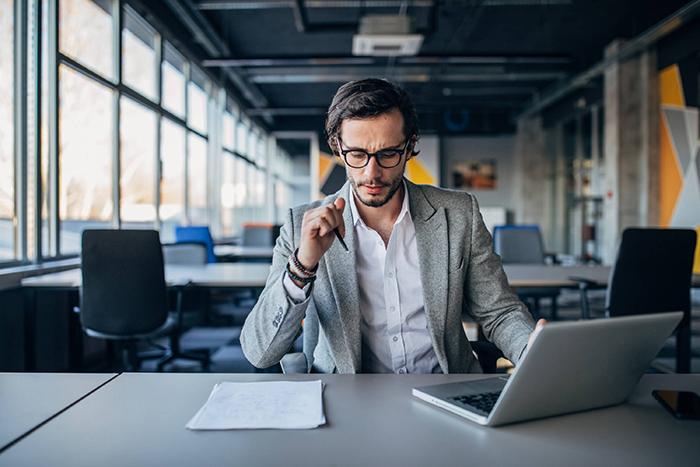 política de vendas - homem em um escritório em frente a uma mesa com notebook e alguns papéis em cima