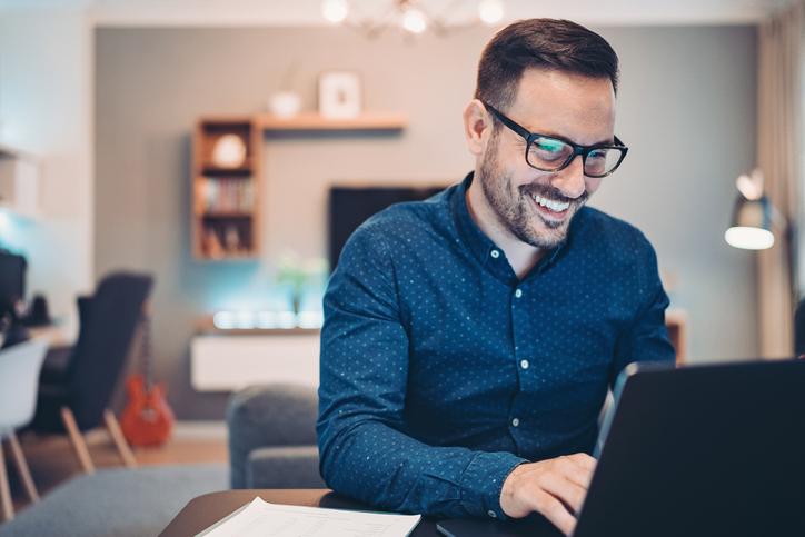 tecnologia e gestão - homem sorrindo na sala de sua casa utilizando um notebook