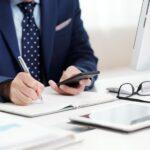 momento certo para trocar de sistema ERP - homem em uma mesa de escritório escrevendo e usando o celular
