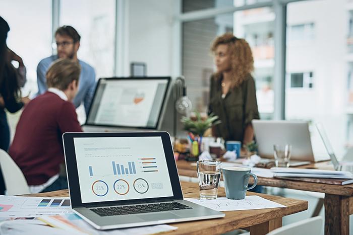 mrr - notebook apresentando gráficos e dados na tela de um notebook em um escritório com funcionários ao fundo conversando