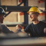 marketing de incentivo - colaboradores de uma indústria utilizando capacete de proteção se cumprimentam com um aperto de mão