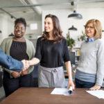 parceiros estratégicos - mulheres de pé em um escritório. Uma delas aperta a mão de um homem.