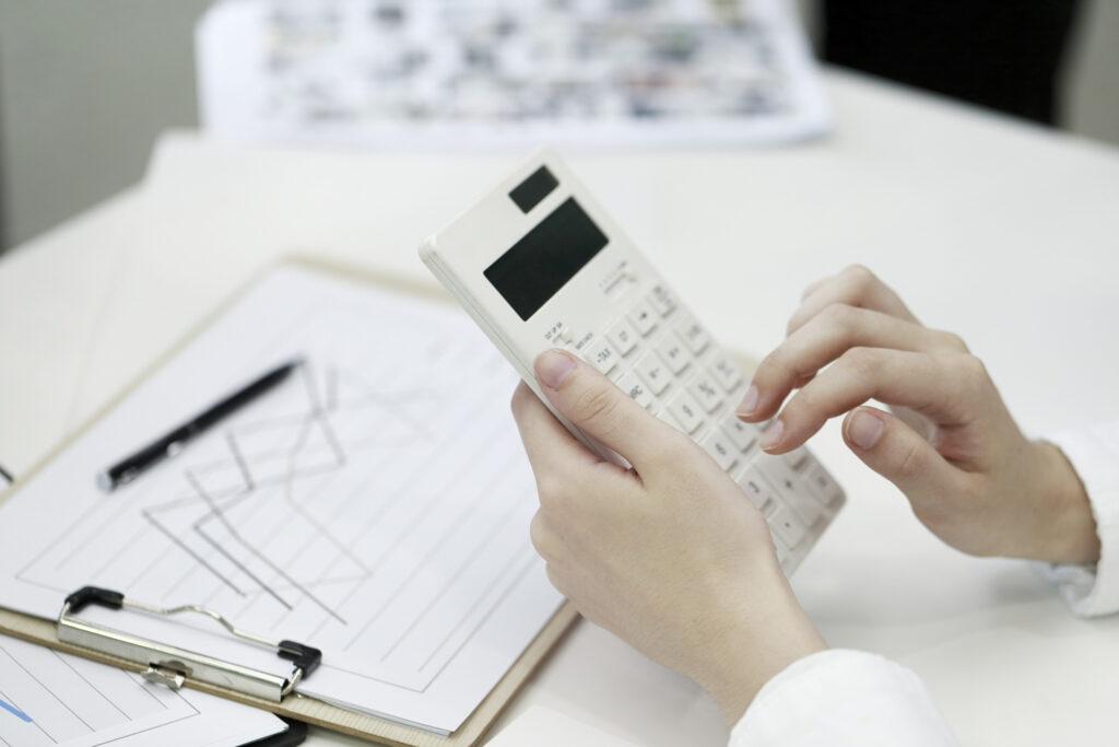 diferença entre markup e margem de contribuição - pessoa utilizando calculadora