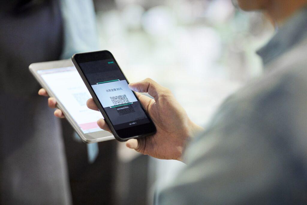 formas de pagamento - pessoa utilizando celular para fazer pagamento via QR code
