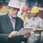 documentos para exportação - homens usando capacete conferindo informações em um tablet