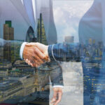 como encontrar compradores no exterior - imagem em dupla exposição de um aperto de mão entre dois homens de terno e uma vista para uma grande cidade com diversos prédios