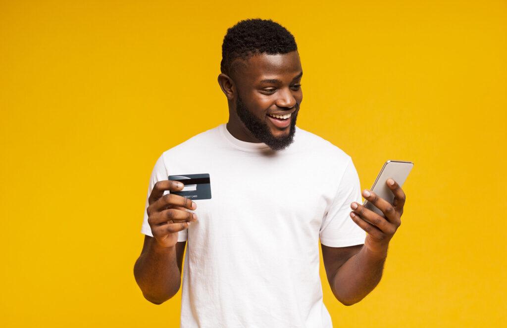 consumidor millennial - homem segurando um cartão de crédito na mão direita e um celular na mão esquerda
