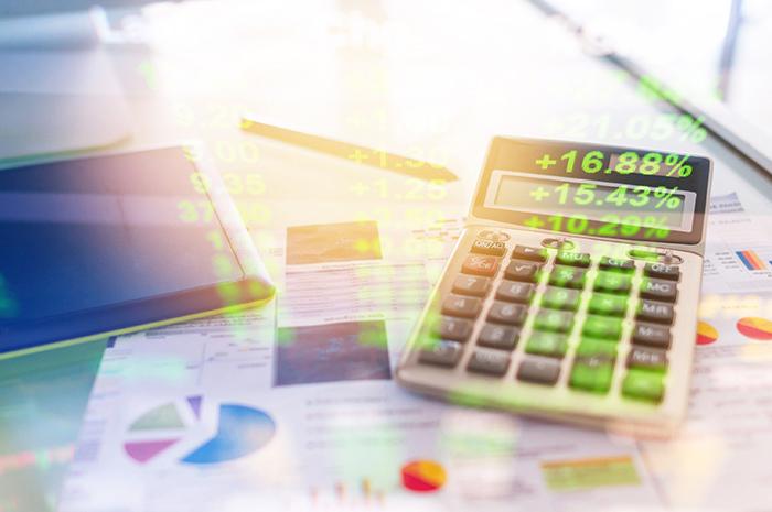 contenção de gastos - imagem em dupla exposição com uma calculadora, folhas com dados e um notebook ao fundo e na frente números percentuais