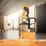 logística de distribuição - homem carregando caixas em um armazém