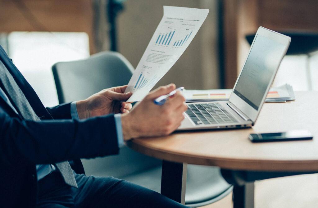 positivação de clientes - homem em uma mesa de escritório analisando dados em uma folha com um notebook em sua frente