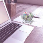estratégia multicanal - notebook e carrinho de compras miniatura ao lado