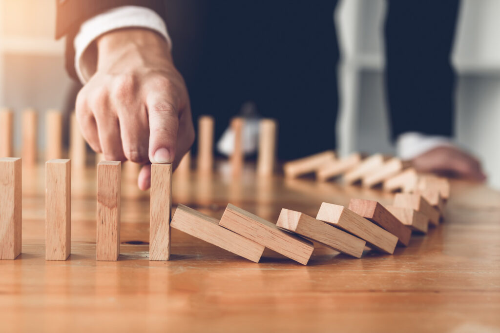 supply chain - imagem com dominós em queda e uma mão segurando os demais da fila para que não caiam