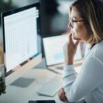 erp mrp wms - mulher em um escritório analisando dados de sistemas de gestão em um computador
