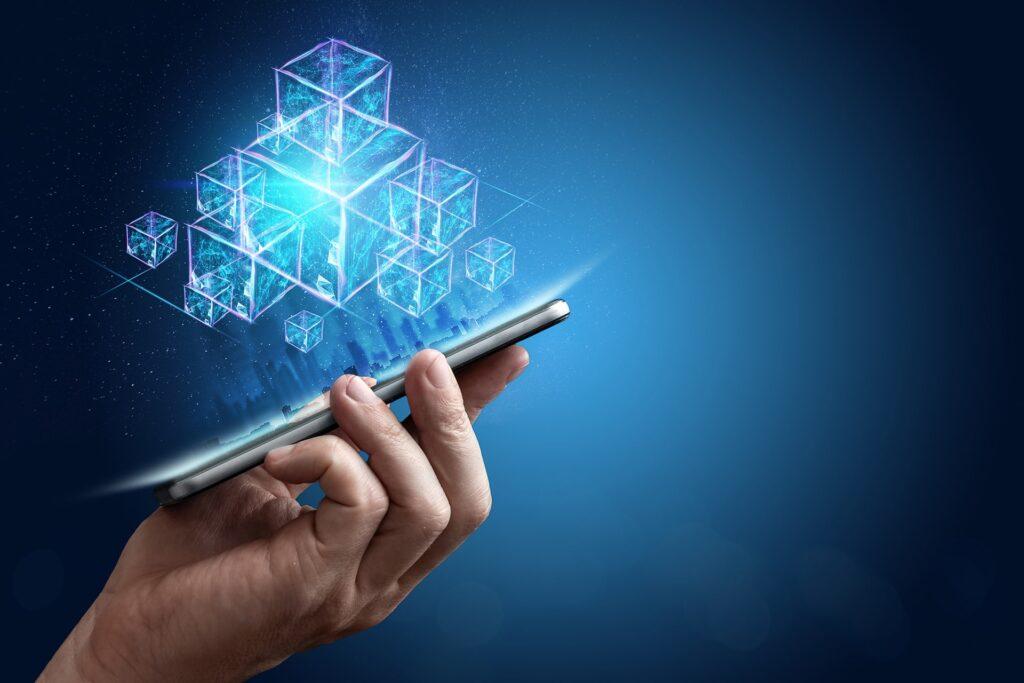 blockchain - imagem ilustrativa com uma mão segurando um celular do qual saem blocos holográficos