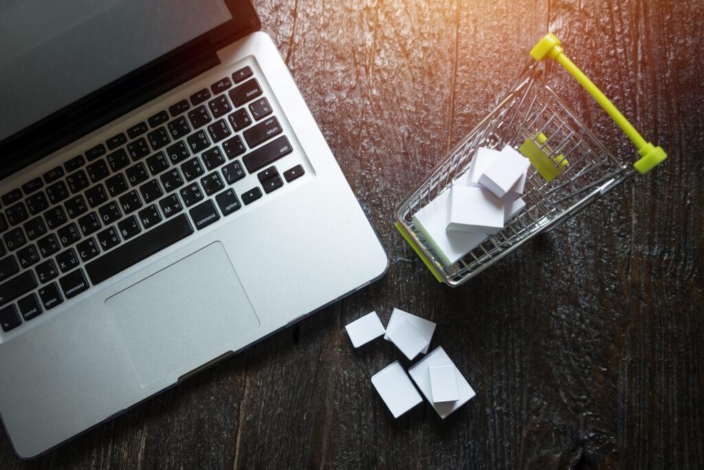 comportamento do consumidor - notebook aberto e ao lado mini carrinho de compras cheio de pacotes