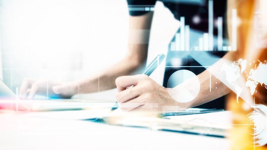 análise de concorrência - pessoa analisando dados e fazendo anotações com uma caneta numa imagem que está sobreposta por gráficos