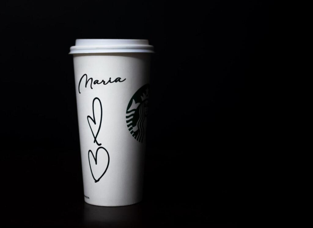 experiência do consumidor - copo de café da Starbucks com um nome do cliente e corações desenhados